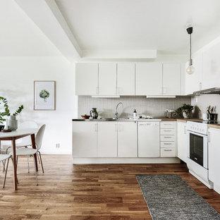 Idéer för ett nordiskt kök, med en integrerad diskho, släta luckor, vita skåp, bänkskiva i rostfritt stål, grått stänkskydd, vita vitvaror och mellanmörkt trägolv