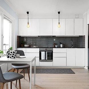 Exempel på ett skandinaviskt svart linjärt svart kök och matrum, med släta luckor, vita skåp, svart stänkskydd, rostfria vitvaror, ljust trägolv och beiget golv