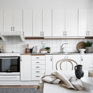 Inspiration för skandinaviska linjära brunt kök och matrum, med en dubbel diskho, luckor med upphöjd panel, vita skåp, vitt stänkskydd, mellanmörkt trägolv och brunt golv