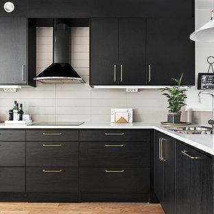 Skandinavisk inredning av ett mellanstort kök, med en dubbel diskho, släta luckor, svarta skåp, beige stänkskydd och mellanmörkt trägolv