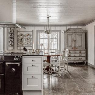 Exempel på ett shabby chic-inspirerat svart svart kök och matrum, med skåp i shakerstil, vita skåp, svarta vitvaror, en halv köksö och grått golv