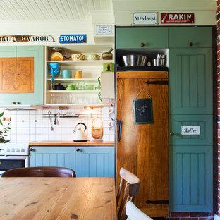 Inspiration för eklektiska linjära kök och matrum, med skåp i shakerstil, blå skåp, vitt stänkskydd och integrerade vitvaror
