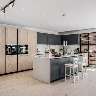 Idéer för ett skandinaviskt vit l-kök, med släta luckor, svarta skåp, svarta vitvaror, ljust trägolv, en köksö och beiget golv