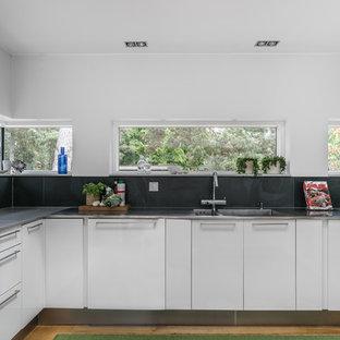 Modern inredning av ett mellanstort u-kök, med vita skåp, en integrerad diskho, släta luckor, mellanmörkt trägolv och brunt golv