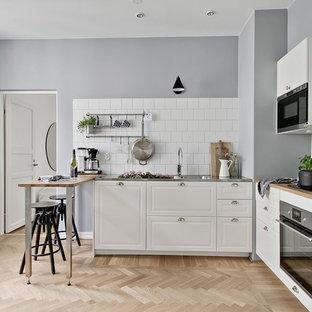 Idéer för att renovera ett avskilt nordiskt brun brunt l-kök, med en integrerad diskho, luckor med upphöjd panel, vita skåp, träbänkskiva, vitt stänkskydd, svarta vitvaror, ljust trägolv och beiget golv