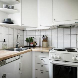 Foto på ett litet nordiskt brun l-kök, med en nedsänkt diskho, släta luckor, vita skåp, träbänkskiva, vitt stänkskydd och vita vitvaror