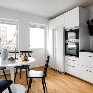 Idéer för minimalistiska svart kök och matrum, med släta luckor, vita skåp, grått stänkskydd, vita vitvaror och ljust trägolv