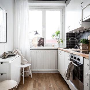 Exempel på ett litet minimalistiskt linjärt kök och matrum, med släta luckor, vita skåp, träbänkskiva, svart stänkskydd, stänkskydd i stickkakel, rostfria vitvaror och mellanmörkt trägolv