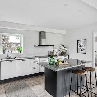 Inredning av ett minimalistiskt grå grått kök, med en enkel diskho, släta luckor, vita skåp, vitt stänkskydd, stänkskydd i tunnelbanekakel, rostfria vitvaror, ljust trägolv och en köksö