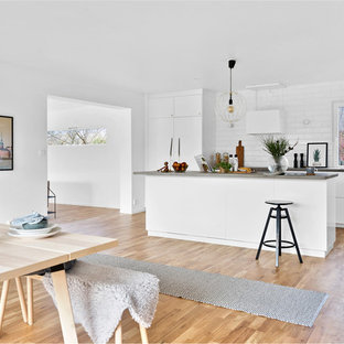 Scandinavian galley kitchen in Malmo with flat-panel cabinets, white cabinets, concrete benchtops, white splashback, ceramic splashback, white appliances, medium hardwood floors and with island.