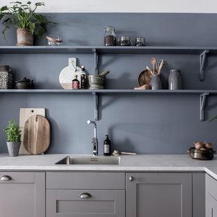 Inredning av ett klassiskt vit vitt kök, med en nedsänkt diskho, skåp i shakerstil, grå skåp och rostfria vitvaror