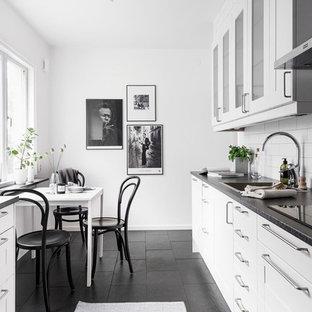 Zweizeilige, Große Nordische Wohnküche ohne Insel mit Einbauwaschbecken, weißen Schränken, Küchenrückwand in Weiß, Rückwand aus Metrofliesen, Glasfronten, Granit-Arbeitsplatte und Keramikboden in Göteborg