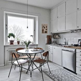 Skandinavisk inredning av ett mellanstort linjärt kök, med släta luckor, vita skåp, träbänkskiva, vitt stänkskydd och målat trägolv