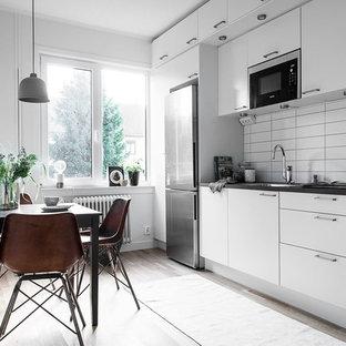 Inspiration för ett mellanstort minimalistiskt linjärt kök och matrum, med en nedsänkt diskho, släta luckor, vita skåp, vitt stänkskydd, stänkskydd i tunnelbanekakel, rostfria vitvaror och ljust trägolv