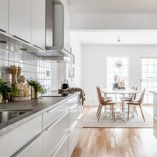Inspiration för minimalistiska grått kök, med släta luckor, vita skåp, vitt stänkskydd, stänkskydd i porslinskakel, laminatgolv, en undermonterad diskho och beiget golv