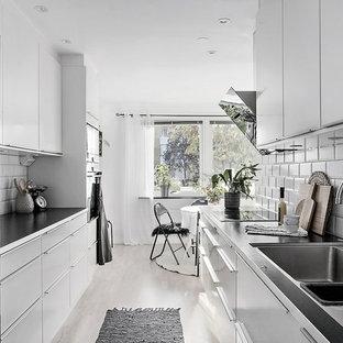 Bild på ett minimalistiskt kök, med en dubbel diskho, släta luckor, vita skåp, vitt stänkskydd, stänkskydd i tunnelbanekakel, rostfria vitvaror och ljust trägolv