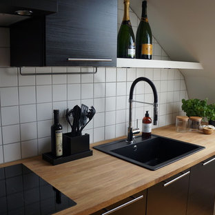 Small modern open concept kitchen photos - Open concept kitchen - small modern open concept kitchen idea in Other with a single-bowl sink, flat-panel cabinets, black cabinets, wood countertops, white backsplash, ceramic backsplash, black appliances and no island