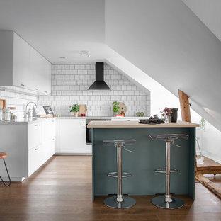 Minimalistisk inredning av ett litet kök, med släta luckor, vita skåp, vitt stänkskydd, en köksö, rostfria vitvaror, mellanmörkt trägolv och brunt golv