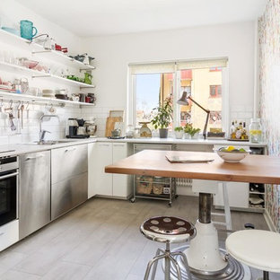 Inspiration for a mid-sized scandinavian l-shaped separate kitchen in Orebro with a double-bowl sink, flat-panel cabinets, white cabinets, white splashback, subway tile splashback, stainless steel appliances, laminate benchtops, limestone floors and no island.