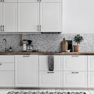 Idéer för ett stort minimalistiskt linjärt kök, med en nedsänkt diskho, luckor med upphöjd panel, vita skåp, grått stänkskydd, stänkskydd i mosaik och målat trägolv
