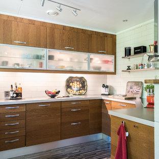 Foto på ett funkis grå u-kök, med släta luckor, bruna skåp, vitt stänkskydd, stänkskydd i tunnelbanekakel, integrerade vitvaror och grått golv