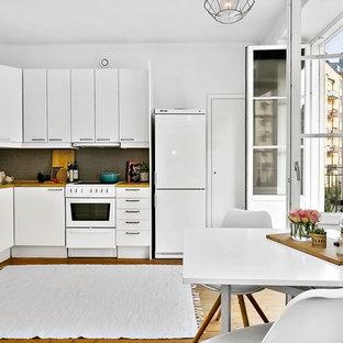 Exempel på ett mellanstort klassiskt kök, med släta luckor, vita skåp, träbänkskiva, vita vitvaror och mellanmörkt trägolv