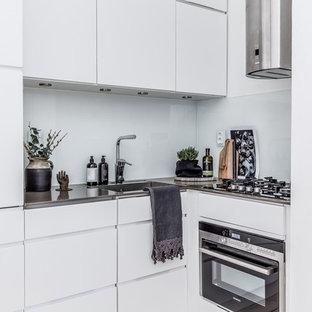 Inredning av ett nordiskt litet grå grått l-kök, med släta luckor, vita skåp, vitt stänkskydd, glaspanel som stänkskydd, en enkel diskho och rostfria vitvaror