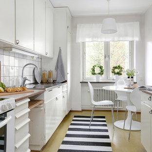 Idéer för att renovera ett nordiskt linjärt kök och matrum, med en integrerad diskho, släta luckor, vita skåp, vitt stänkskydd, vita vitvaror och gult golv