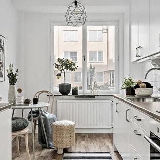 Idéer för skandinaviska brunt parallellkök, med en nedsänkt diskho, släta luckor, vita skåp, vitt stänkskydd, rostfria vitvaror och brunt golv