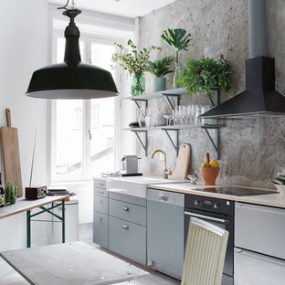 Small industrial eat-in kitchen inspiration - Eat-in kitchen - small industrial single-wall eat-in kitchen idea in Stockholm with flat-panel cabinets, gray cabinets, wood countertops and no island
