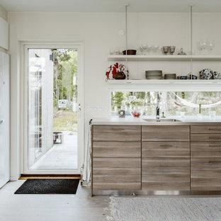 Skandinavisk inredning av ett mellanstort kök, med släta luckor och skåp i slitet trä