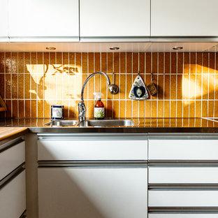 Diseño de cocina retro, pequeña, con salpicadero naranja
