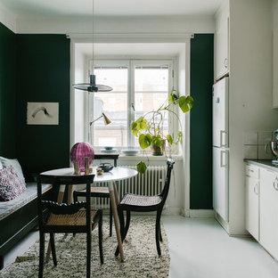 Nordisk inredning av ett mellanstort linjärt kök med öppen planlösning, med släta luckor, vita skåp, bänkskiva i rostfritt stål, vitt stänkskydd, stänkskydd i porslinskakel, vita vitvaror, betonggolv, vitt golv och en integrerad diskho