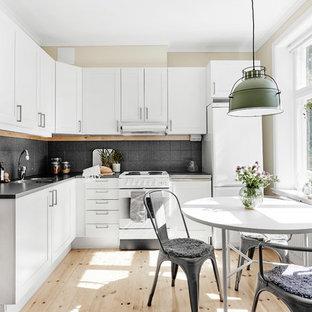 Exempel på ett minimalistiskt kök, med skåp i shakerstil, vita skåp, grått stänkskydd, vita vitvaror, ljust trägolv och beiget golv