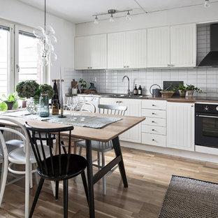 Skandinavisk inredning av ett mellanstort linjärt kök och matrum, med en dubbel diskho, vita skåp, träbänkskiva, vitt stänkskydd, svarta vitvaror, mellanmörkt trägolv och brunt golv