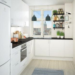 Idee per una cucina a L moderna chiusa e di medie dimensioni con ante lisce, ante bianche, top in laminato, elettrodomestici in acciaio inossidabile, parquet chiaro e nessuna isola