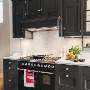 Cette image montre une grande cuisine linéaire victorienne avec un placard avec porte à panneau encastré, des portes de placard noires, une crédence grise, un électroménager noir, un sol en bois clair, un plan de travail en marbre et aucun îlot.