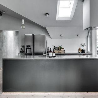 Foto på ett mellanstort industriellt kök, med en enkel diskho, marmorbänkskiva, rostfria vitvaror, ljust trägolv och en köksö