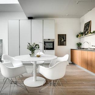 Exempel på ett stort skandinaviskt kök, med släta luckor, rostfria vitvaror, ljust trägolv, beiget golv, skåp i mellenmörkt trä och vitt stänkskydd
