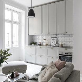 Exempel på ett minimalistiskt grå linjärt grått kök med öppen planlösning, med en undermonterad diskho, skåp i shakerstil, grå skåp, vitt stänkskydd, stänkskydd i tunnelbanekakel, integrerade vitvaror, ljust trägolv och beiget golv
