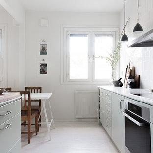 Nordisk inredning av ett mellanstort linjärt kök och matrum, med skåp i shakerstil, gröna skåp, vitt stänkskydd, ljust trägolv och en köksö