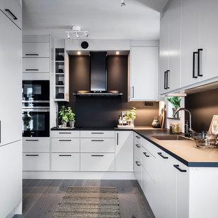 Inredning av ett minimalistiskt stort kök, med en integrerad diskho, släta luckor, vita skåp, svart stänkskydd, svarta vitvaror, grått golv och ljust trägolv