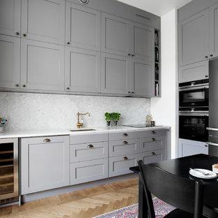 Foto på ett mellanstort vintage kök, med en undermonterad diskho, skåp i shakerstil, marmorbänkskiva, rostfria vitvaror och ljust trägolv