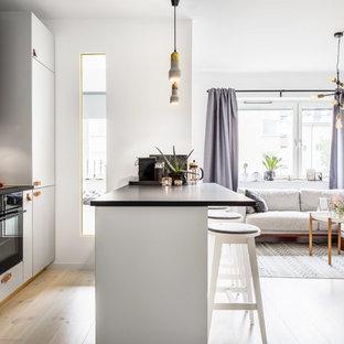 Bild på ett mellanstort skandinaviskt linjärt kök med öppen planlösning, med släta luckor, vita skåp, vitt stänkskydd, svarta vitvaror, ljust trägolv och en halv köksö