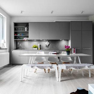 Foto på ett mellanstort minimalistiskt linjärt kök och matrum, med släta luckor, grå skåp, grått stänkskydd och ljust trägolv