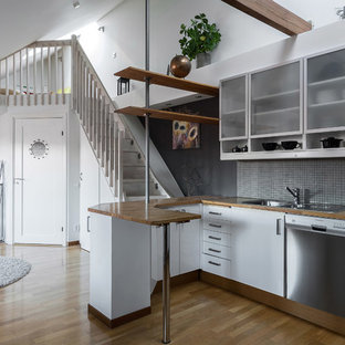 Foto på ett skandinaviskt brun kök, med en dubbel diskho, släta luckor, vita skåp, träbänkskiva, grått stänkskydd, stänkskydd i mosaik, rostfria vitvaror, mellanmörkt trägolv, en halv köksö och brunt golv