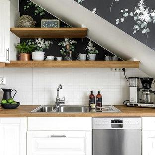 Inspiration för ett minimalistiskt l-kök, med en dubbel diskho, luckor med upphöjd panel, vita skåp, träbänkskiva, vitt stänkskydd, stänkskydd i tunnelbanekakel och rostfria vitvaror