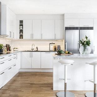 Idéer för ett klassiskt l-kök, med släta luckor, vita skåp, vitt stänkskydd, stänkskydd i tunnelbanekakel, rostfria vitvaror, mellanmörkt trägolv, en köksö och brunt golv