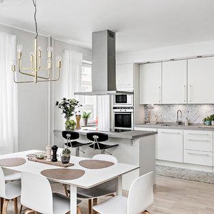 Exempel på ett minimalistiskt kök, med en undermonterad diskho, släta luckor, vita skåp, grått stänkskydd, stänkskydd i sten, rostfria vitvaror, ljust trägolv, en halv köksö och beiget golv