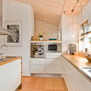 Große Skandinavische Küche in L-Form mit Einbauwaschbecken, flächenbündigen Schrankfronten, weißen Schränken, Arbeitsplatte aus Holz, Küchenrückwand in Weiß, Küchengeräten aus Edelstahl, Kücheninsel und Terrakottaboden in Malmö